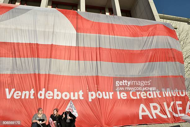 People sit under a banner reading 'headwind for employment' on January 24 in front of the townhall of Brest northwestern France during a...