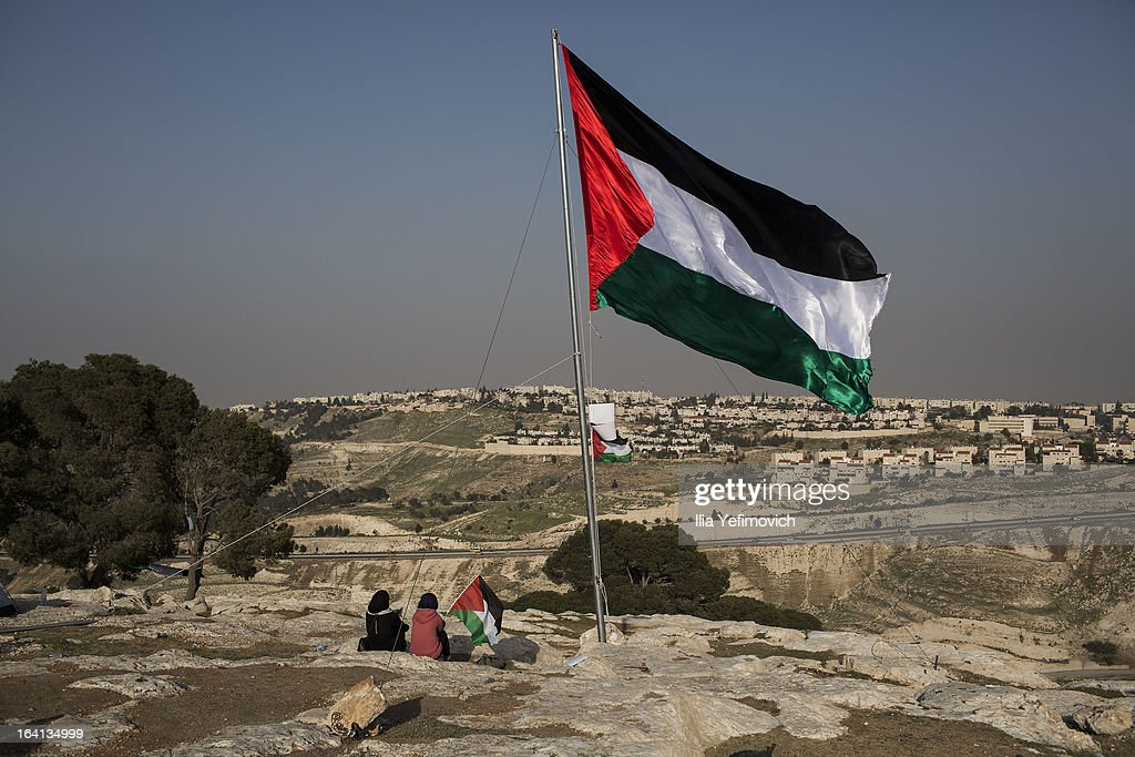 MA'ALE, ADUMIM, WEST-BANK - MARCH 20: People sit under a giant Palestinian flag as Palestinians erect protest tents in a camp on March 20, 2013 in the E1 area next to Ma'ale Adumim. The action took place at the same time as U.S. President Barack Obama arrived to Ben Gurion airport near Tel Aviv. This will be Obama's first visit as President to the region, and his itinerary will include meetings with the Palestinian and Israeli leaders as well as a visit to the Church of the Nativity in Bethlehem.
