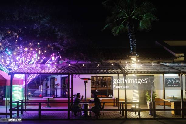 People sit under a heater at a restaurant in the Old Town neighborhood of San Diego, California, U.S., on Thursday, Nov. 19, 2020. California...