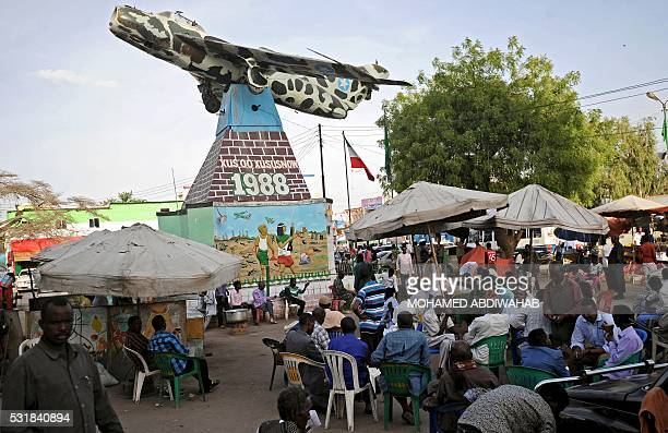 People sit under a russian made MIG fighter jet that was used in 1988 hanging in Hargeisa as monument and reminder to the people of Somaliland of...