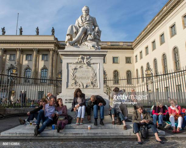 People sit under a statue of Alexander von Humboldt as they wait for the beginning of a free openair concert conducted by Daniel Barenboim in which...