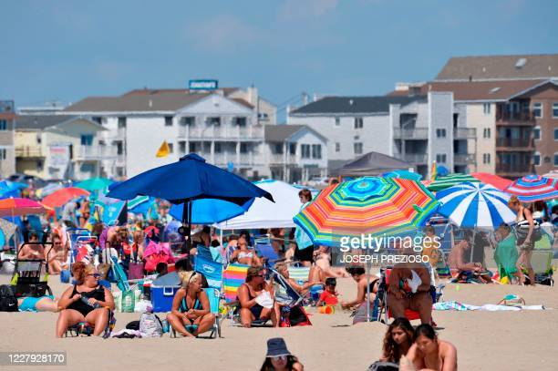 People sit under umbrellas on the sand at Hampton Beach in Hampton New Hampshire on August 5 as COVID19 cases in New England are on the rise Hampton...