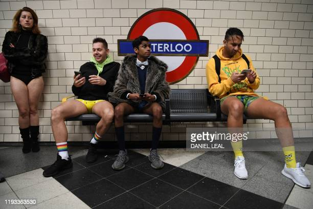 People sit waiting for a train at Waterloo Underground station as they take part in the annual 'No Trousers On The Tube Day' in central London on...