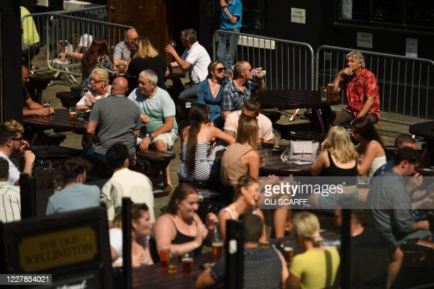 """People sit with drinks at outdoor seating at a pub in the centre of Manchester, northwest England, on July 31, 2020. - Britain on Friday """"put the..."""