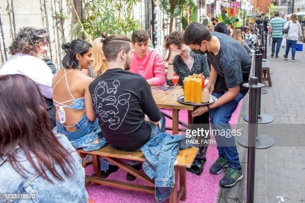 People sit with their drinks at a table outside a re-opened pub in Dublin, on June 7 as bars, restaurants and cafes resumed outdoor service as part...