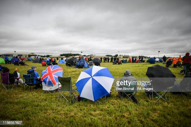 People sit with umbrellas at the Royal International Air Tattoo, RAF Fairford, as bad weather including strong winds, low cloud and rain have...