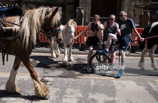 People sito n a trap as they watch horses and riders pass by on Battlebarrow Street on the opening day of the annual Appleby Horse Fair in the town...
