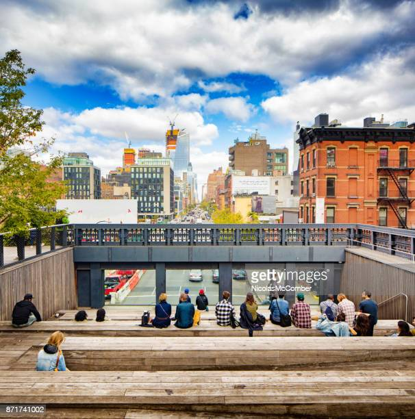 people sitting and enjoying the view at the high line park in new-york city - chelsea new york stock photos and pictures