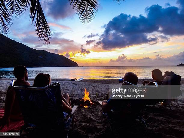 People sitting around bonfire on calm beach at dusk