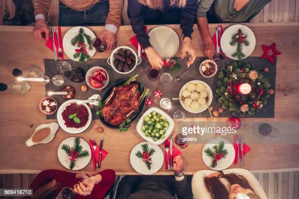 Leute sitzen herum und Weihnachtstisch mit traditioneller deutscher Küche