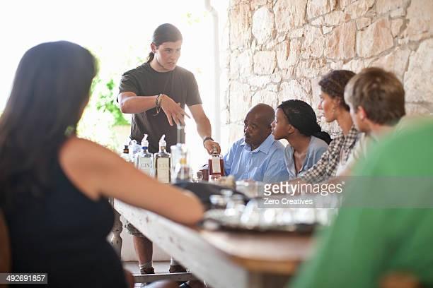 People sitting around table, tasting drinks