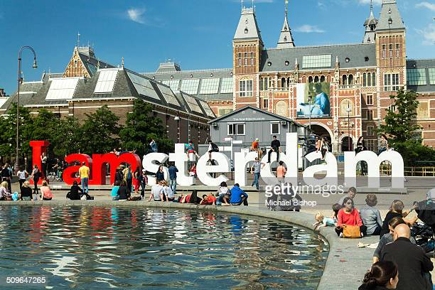 People sitting around the pool and playing in and around the I Amsterdam sign in Amsterdam Netherlands
