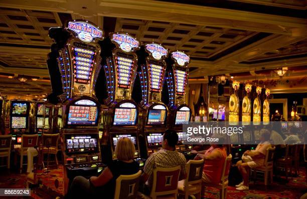 People sitting at a bank of slot machines at the Wynn Hotel and Casino is seen in this 2009 Las Vegas, Nevada, interior photo.