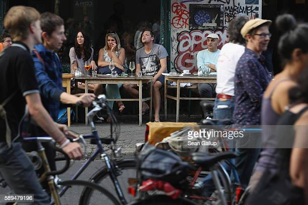 People sitting at an outdoor cafe in Oranienstrasse in Kreuzberg district watch as people demonstrating for women's rights walk past on a warm summer...