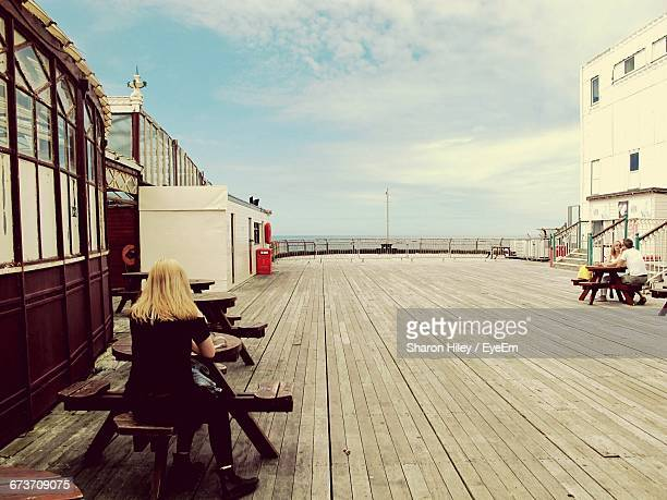 people sitting at table on north pier against cloudy sky - blackpool stock pictures, royalty-free photos & images
