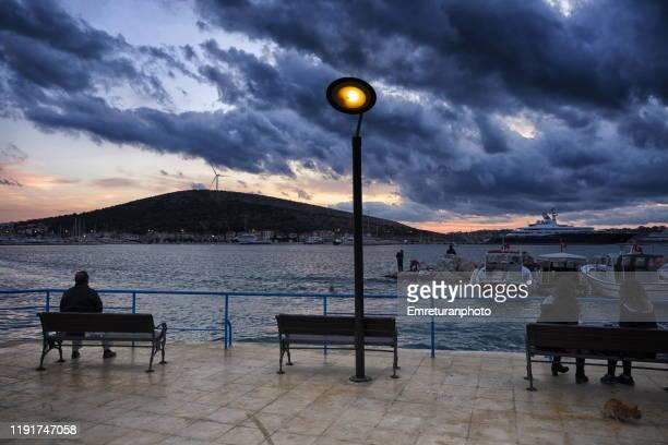 people sitting at the seafront against a dramatic winter sky in cesme bay. - emreturanphoto bildbanksfoton och bilder