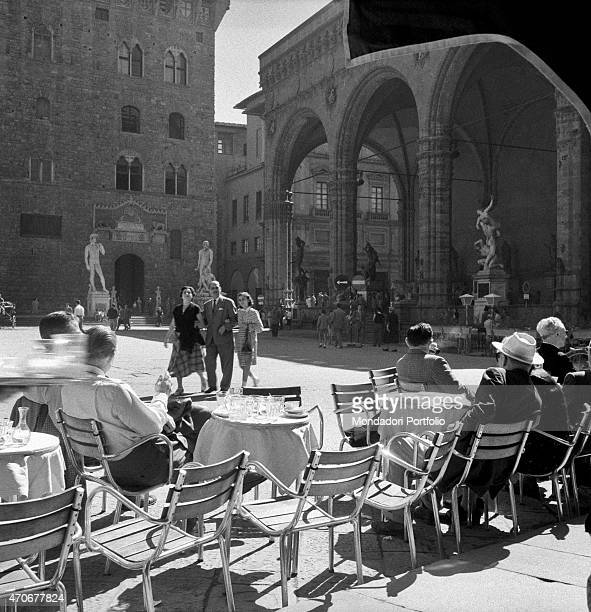 'People sitting at the table of a caf on Piazza della Signoria In front of them Palazzo Vecchio and the Loggia dei Lanzi Florence 1950s '