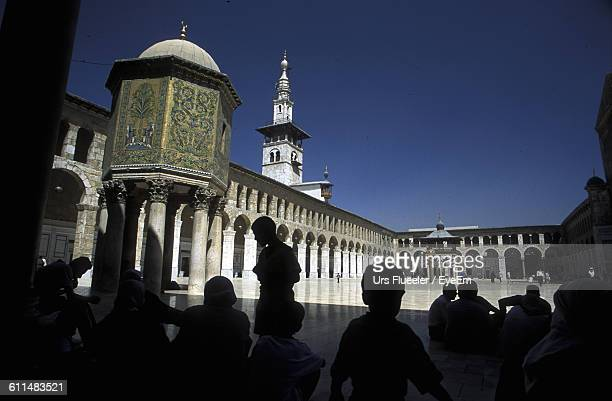 People Sitting At Umayyad Mosque Against Clear Sky