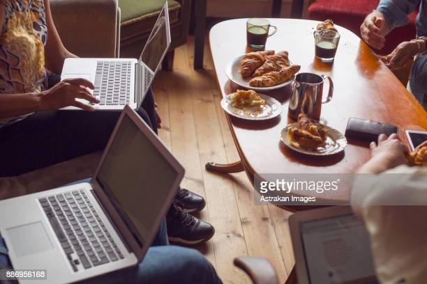People sitting by coffee table with laptops or smart phones