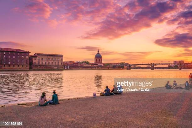 People Sitting By River Against Dramatic Sky During Sunset