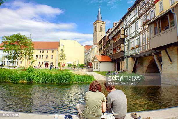 people sitting by river with buildings in background - erfurt stock-fotos und bilder