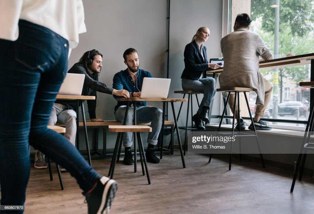 People Sitting Down And Working Together In A Busy Cafe : Stock Photo