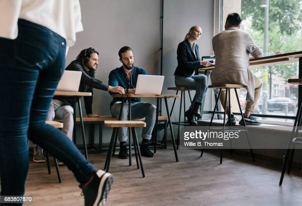 People Sitting Down And Working Together In A Busy Cafe