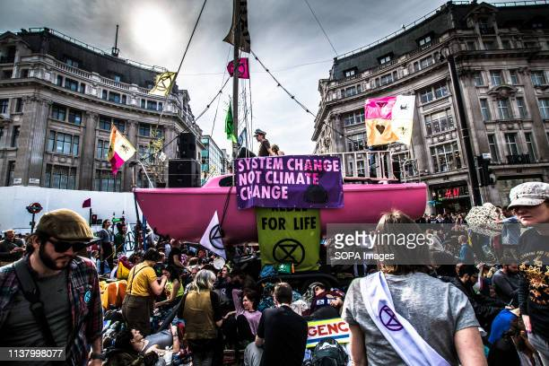 People sitting down in front of the boat which blocks the street in Oxford Circus during the Extinction Rebellion Strike in London Extinction...