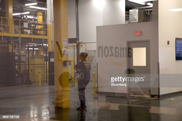 People sitting in a classroom are reflected in a window as a worker arrives at the Amazoncom Inc fulfillment center in Robbinsville New Jersey US on...