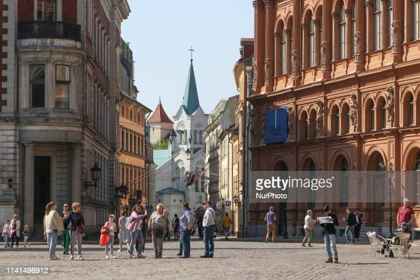 People sitting in a open air restaurants and walking by the Old town Livu Square are seen in Riga Latvia on 28 April 2019