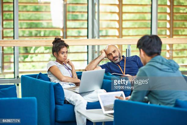 People sitting in blue armchairs in modern office.