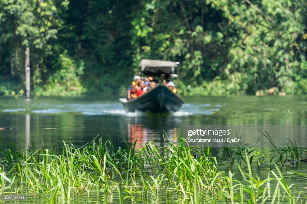 People Sitting In Boat On Lake Against Trees : Stock Photo