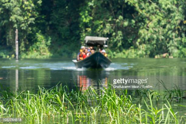 People Sitting In Boat On Lake Against Trees