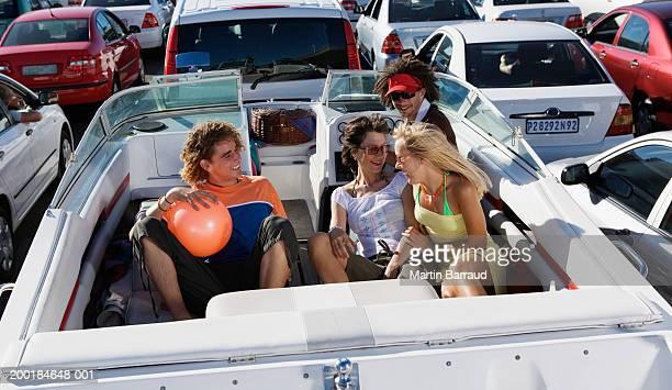 People sitting in boat on trailer in traffic jam