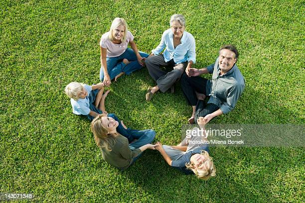 People sitting in circle on grass holding hands looking up at camera