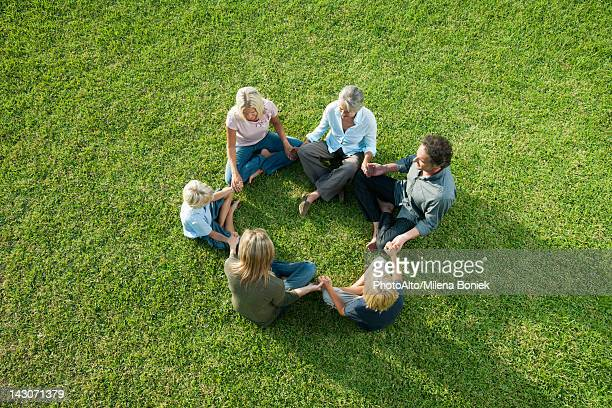 People sitting in circle on grass holding hands