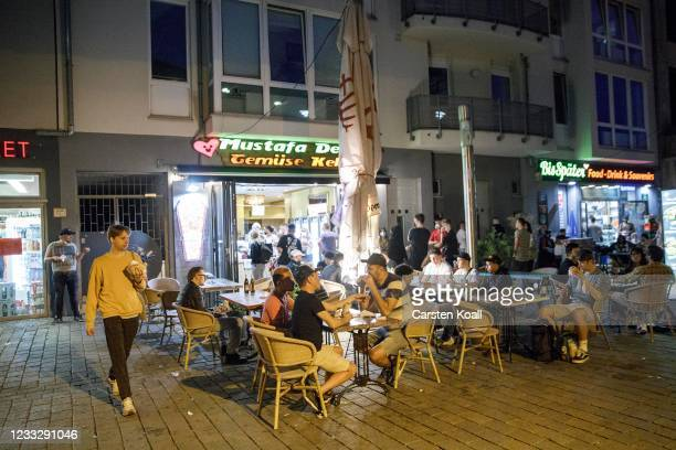 People sitting in front of a food shop at Hackescher Market on the second day that people are no longer required to show a negative Covid test result...