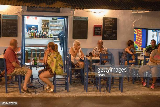 People Sitting in Front of a Pub in Pithagorio, Greece