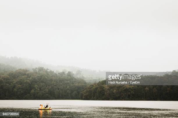 People Sitting In Inflatable Duck On River By Trees Against Sky