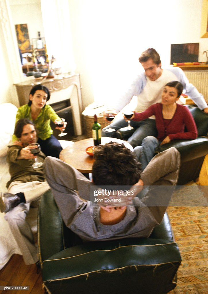 People sitting in living room, drinking wine : Stock Photo