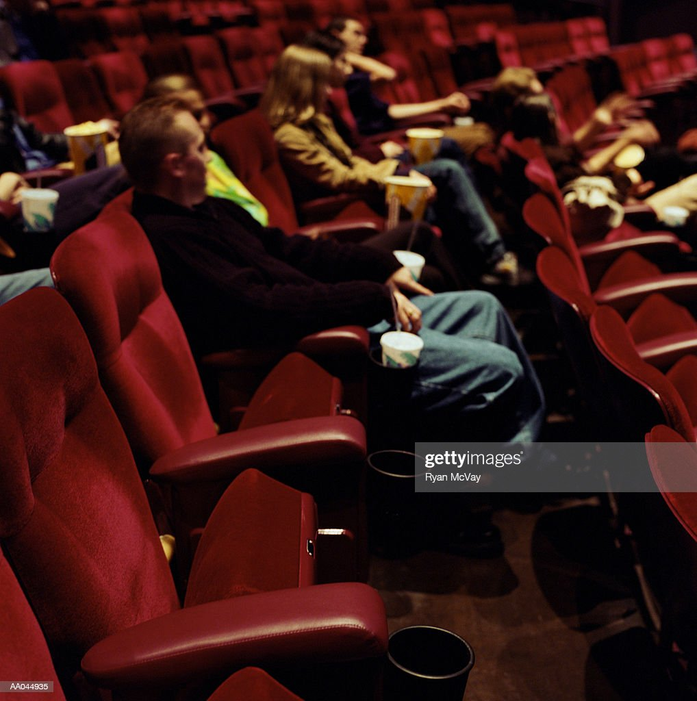 People sitting in movie theater, side view : Stock Photo