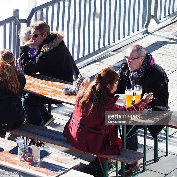 People sitting in sunshine and highest beergarden of Germany