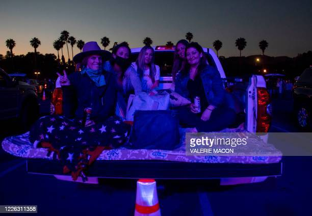 People sitting in the back of a truck pose as they listen to US country singer Randy Houser perform during the drive-in live music event 'Concerts in...