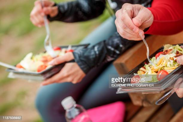 people sitting in the park, eating a healthy protein salad from a plastic casing - plastic plate stock photos and pictures