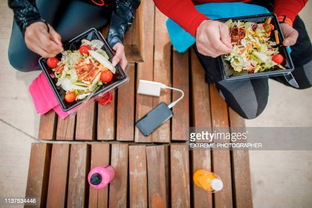 people sitting in the park side by side, eating a healthy protein salad from a plastic casing, a towel, bottled sport drinks and a mobile phone hooked to a power bank between them - plastic plate stock photos and pictures