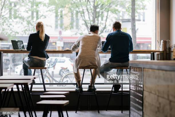 people sitting in the window of a cafe working - city life stock pictures, royalty-free photos & images