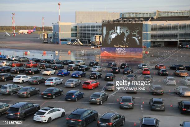 People sitting in their cars watch a movie at the Autokino drive-in cinema on an airfield of the airport in Vilnius on April 29, 2020. - Hundreds of...