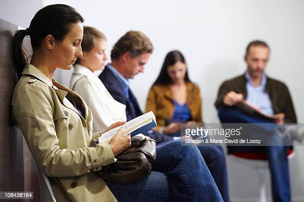 people sitting in waiting room - waiting room stock pictures, royalty-free photos & images