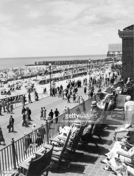 People sitting on a balcony overlooking the boardwalk on warm summer day Atlantic City New Jersey mid to late 1920s