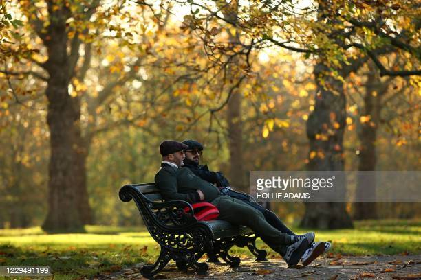 People sitting on a bench, chat beneath the autumn colours of trees in Green Park in London on November 6 as the second lockdown comes into force in...